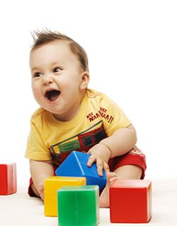 boy smiling playing with blocks