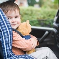 boy sitting in car seat with stuffed bear